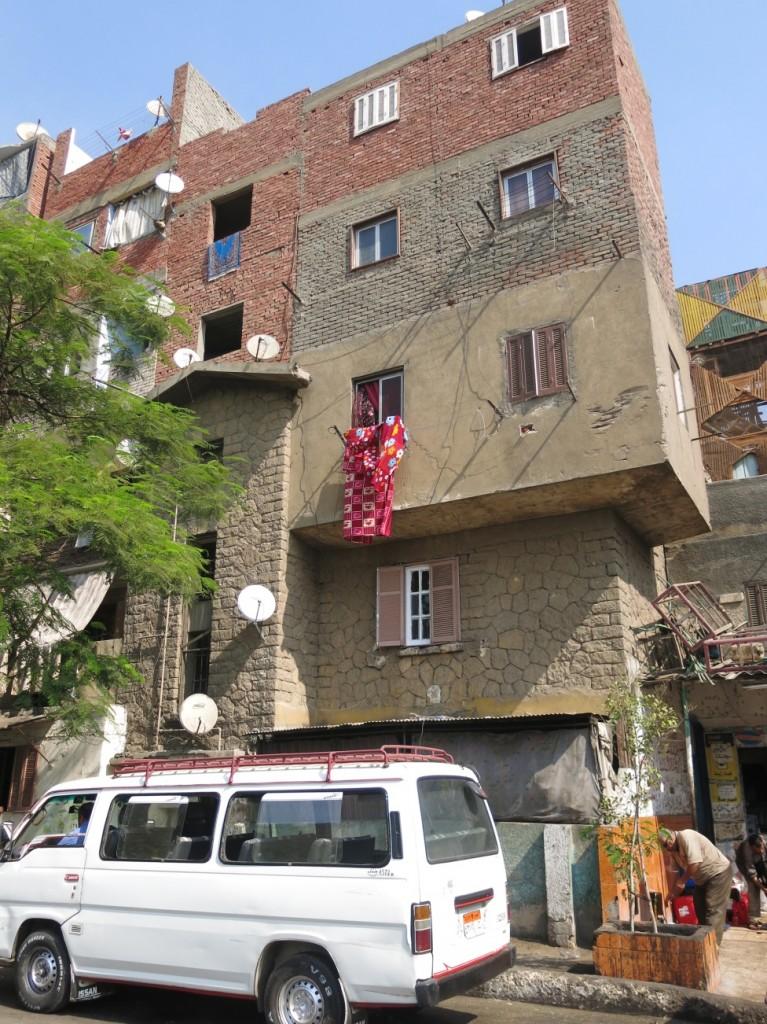 التعليات اللارسمية لمباني مدينة العمال، حيث يظهر المبنى الأصلي بواجهته الحجرية والطوابق العليا المبنية بالطوب الأحمر. (تضامن،2015).