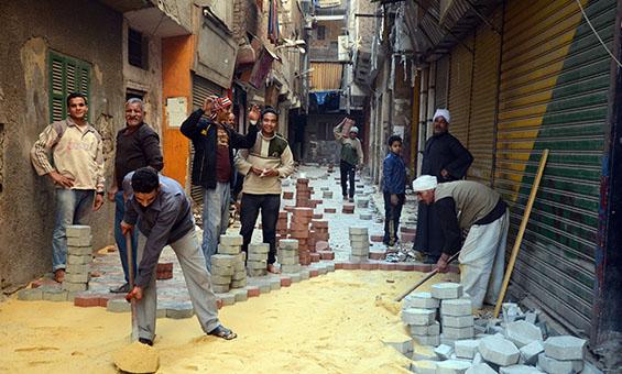 """سكان ميت عقبة يقومون برصف أحد شوارع المنطقة ببلاط """"انترلوك"""" تصوير: تضامن 2013-ب"""