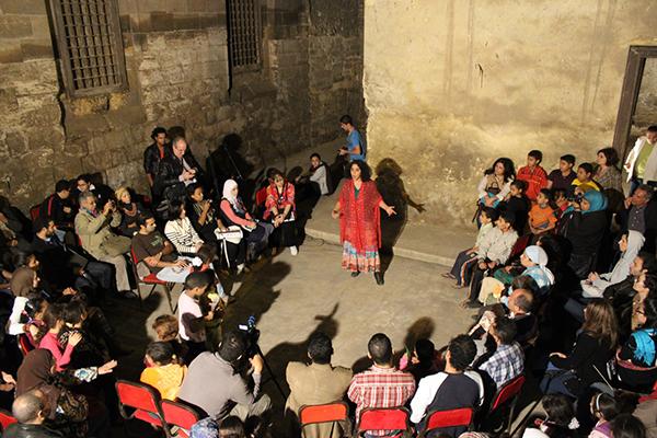 """عرض حكي مسرحي بعنوان """"الخليفة من جوة لبرة""""، حضوره من أهل الخليفة والزوار من جميع أنحاء القاهرة.المصدر: مبادرة الأثر لنا، بدون تاريخ."""