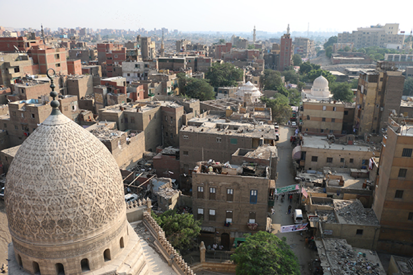 A photo of al-Khalīfa Street, taken from the top of al-Sayyida Sukayna Mosque's minaret. It shows the al-Sayyida Ruqayya Dome, the Shajarat al-Durr Dome and the adjacent al-Khalīfa service center (al-Mustaūṣaf), among residential buildings. Source: Athar Lina Initiative. n.d.