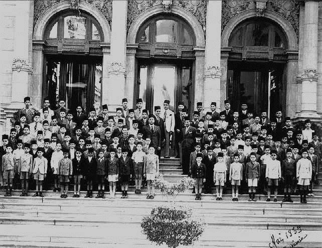 تلاميذ مدرسة الناصرية في صورة مدرسية التقطت في أيار/ مايو 1939. الأقواس فوق المداخل وأحجار العقد المنحوتة في الخلفية تشي بالأصول الفخمة للبناء. المصدر: sakeb600 – نسخة من - SA 2.0