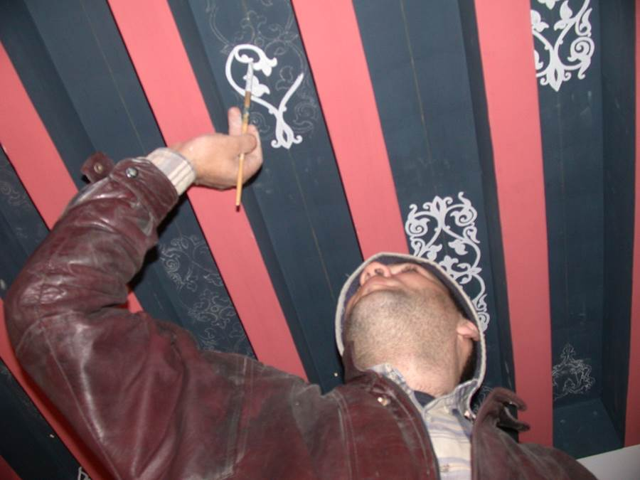 أحد أعضاء فريق الترميم يعمل على أحد أعمال الزخرفة والزينة في مدرسة درب شغلان