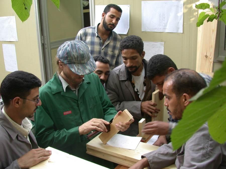 مدرب أعمال خشبية يشرح لحرفين محليين كيفية استخدام أداة القياس والعلام (الشنكار). المصدر: صندوق الآغا خان للثقافة